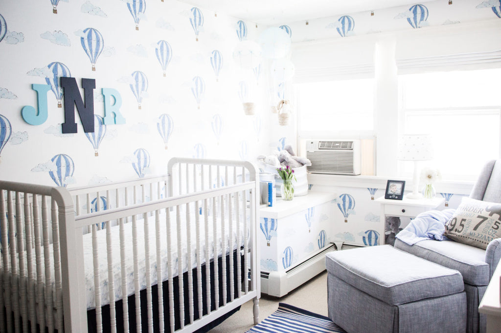 White crib in white and blue interior, boy's nursery styling.