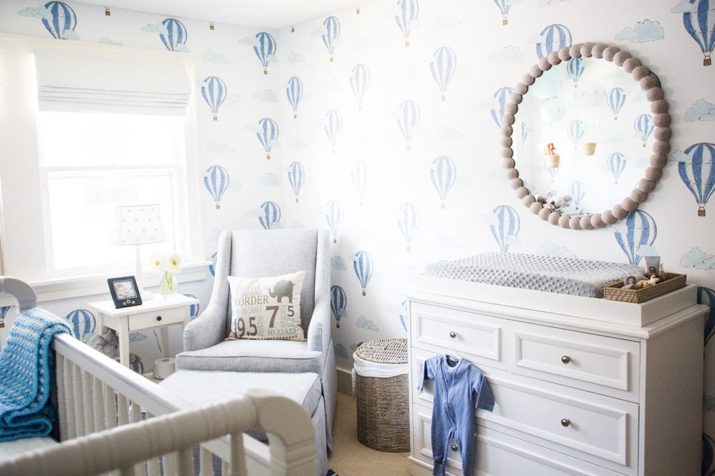 Boy's nursery with blue accents and white wood furniture.