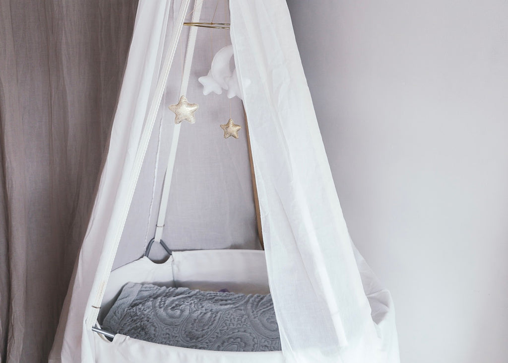 White bassinet with white canopy and stars and clouds mobile