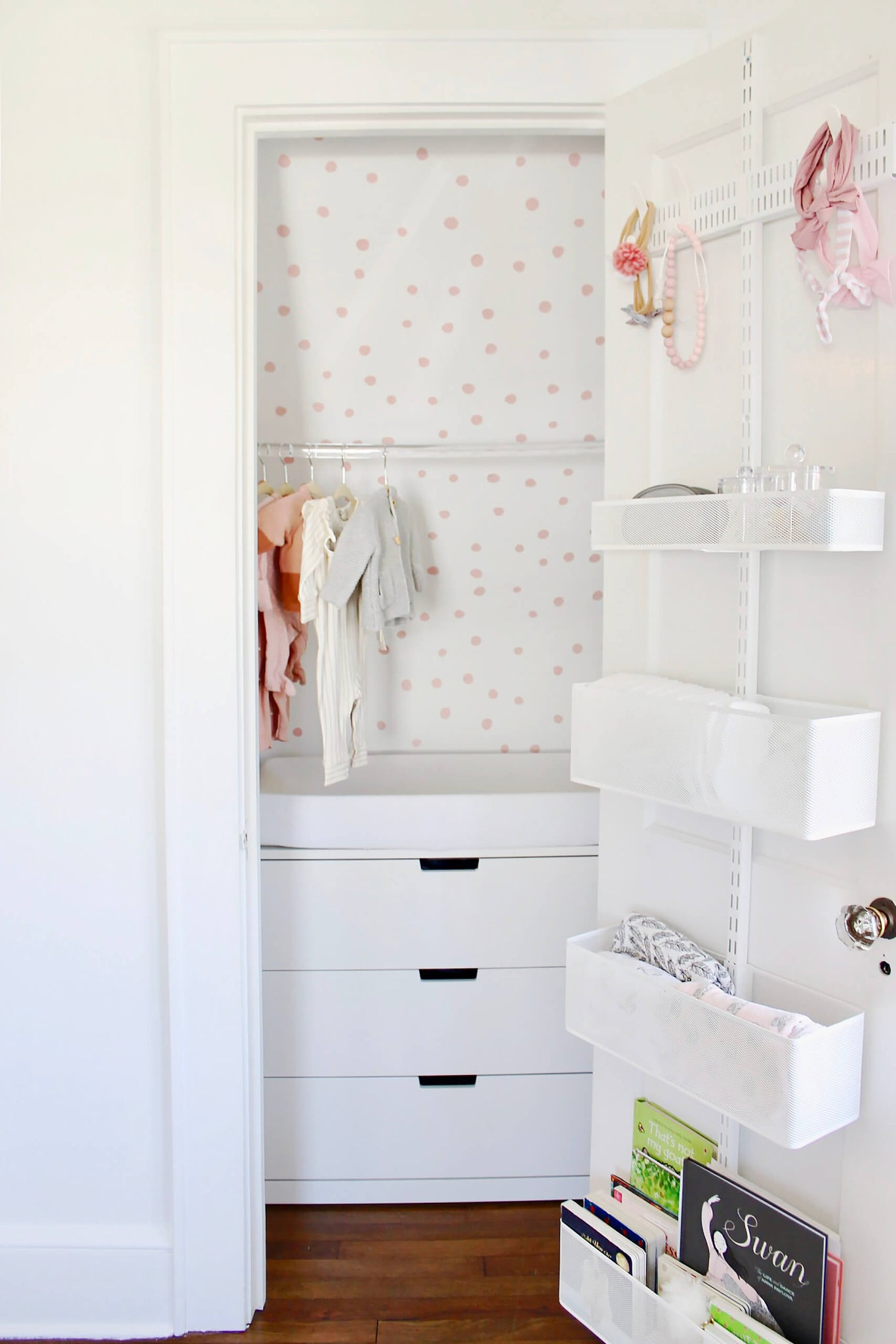 White and pink tiny walk in closet in baby girl nursery with clear rod for hangers