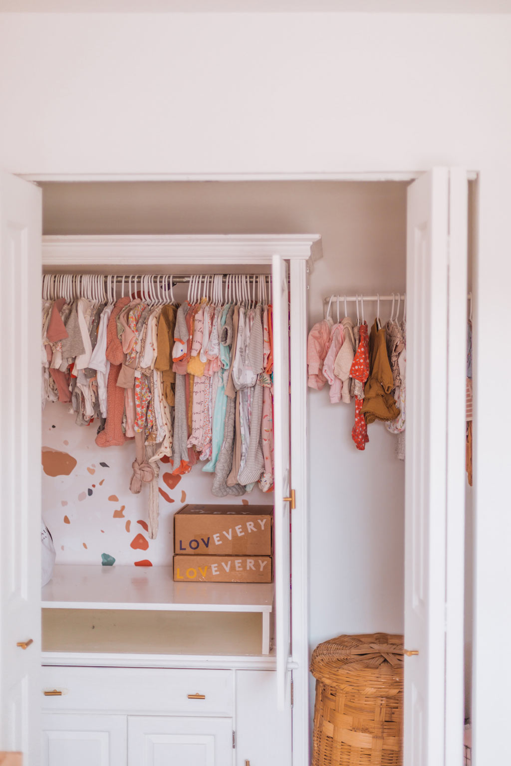 Baby nursery closet design with terrazzo feature wall and warm color palette baby clothing