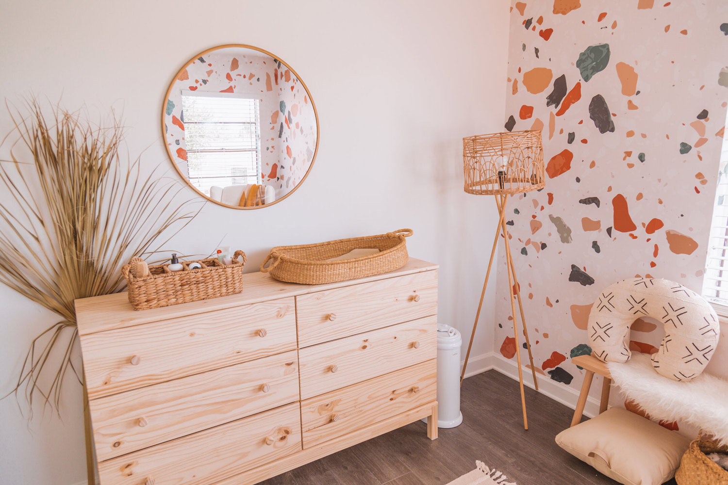 Baby nursery changing table with round mirror and dried palm leaf decor