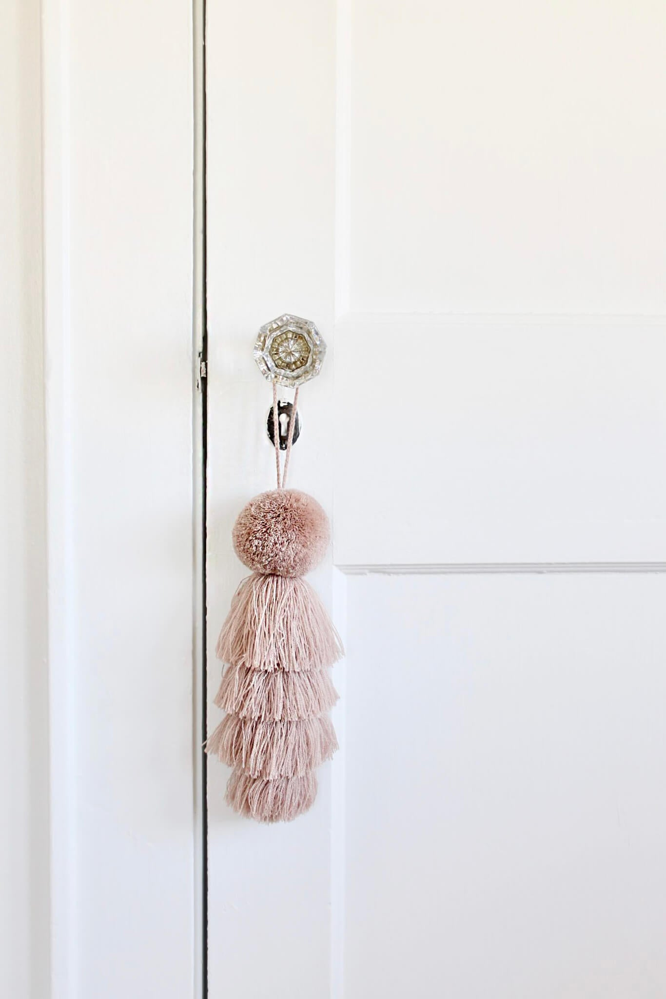 Blush pink tassel on glass door knob in white baby girl nursery interior