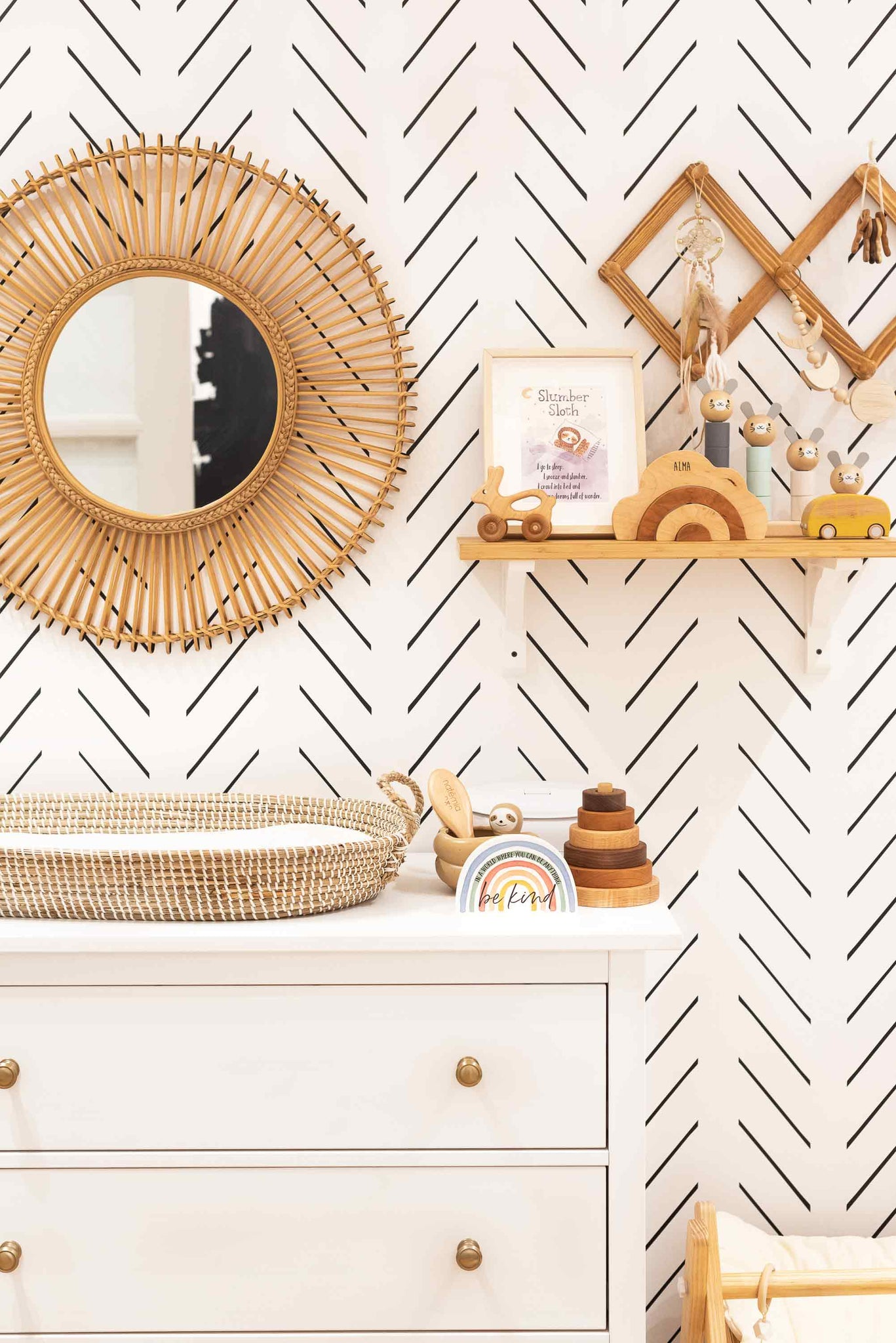 Baby changing table on a white dresser with rattan and wood interior decor and round accent mirror