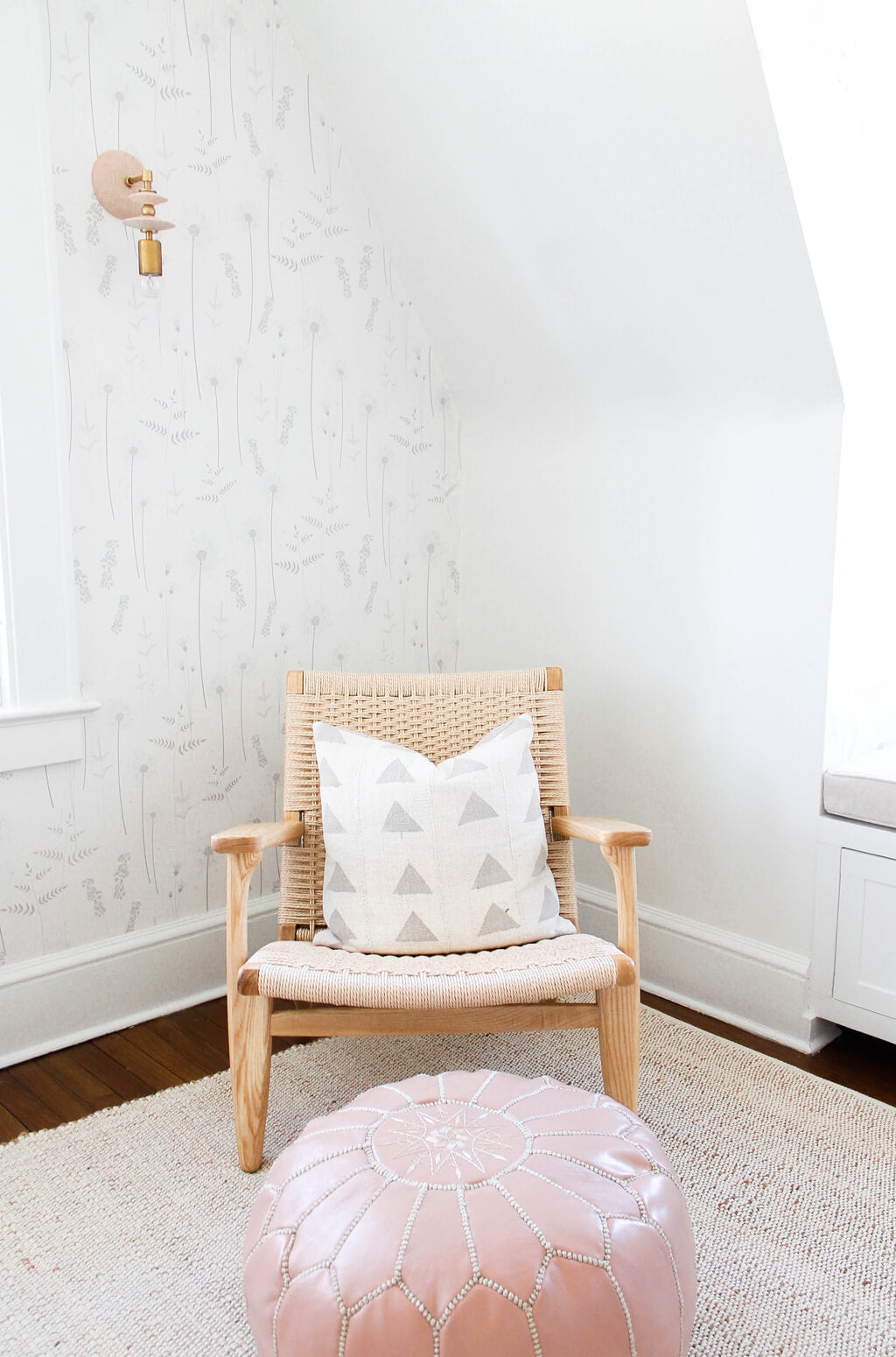 Rattan nursing chair in white baby girl nursery with floral wallpaper and geometric throw pillow and pink moroccan pouf
