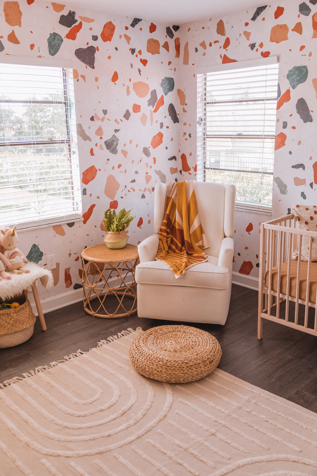Modern coastal bohemian style baby girl nursery interior design with warm tone terrazzo removable wallpaper and light wood furniture