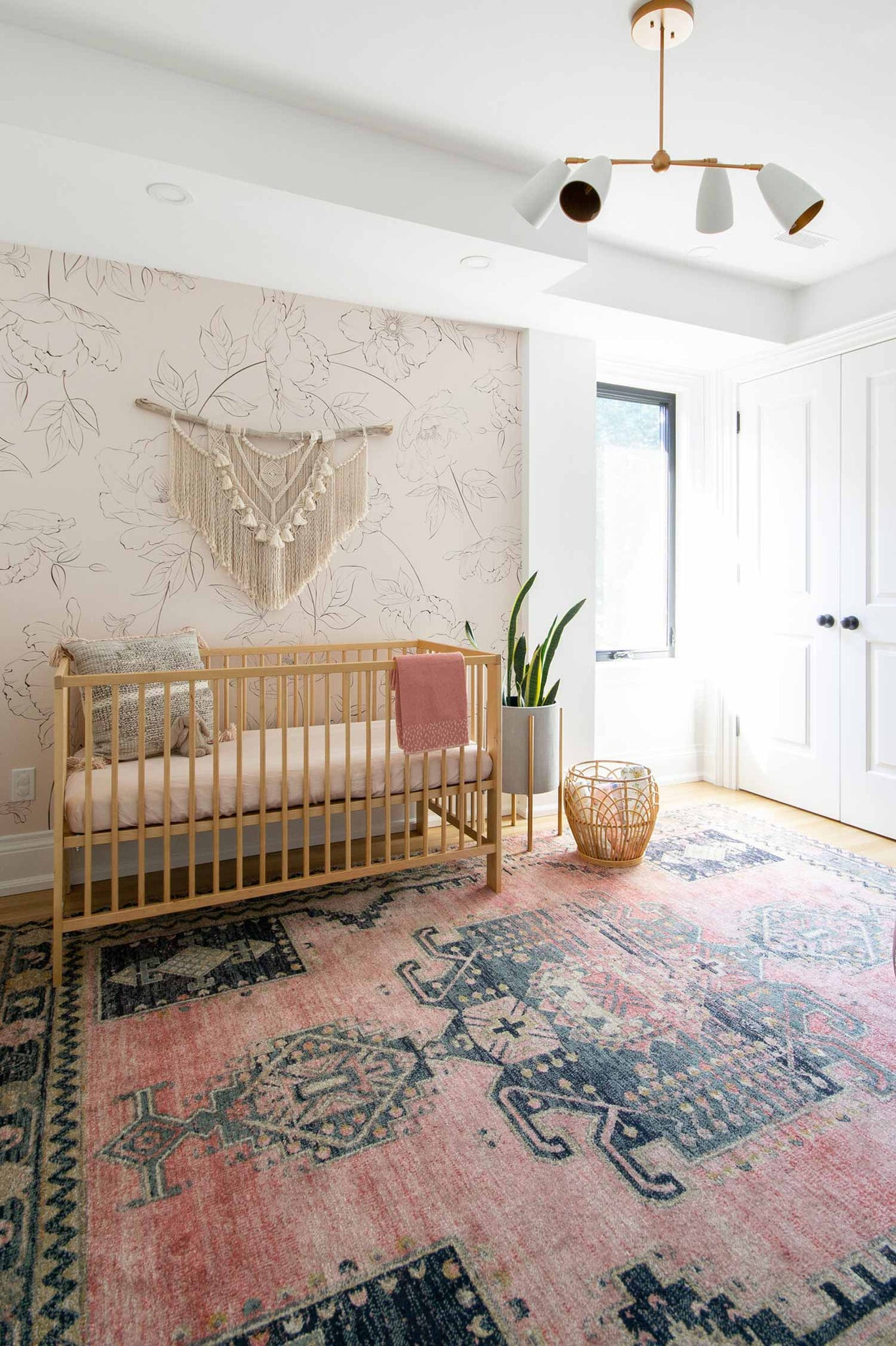 Modern and girly bohemian style nursery interior with floral removable wallpaper behind crib