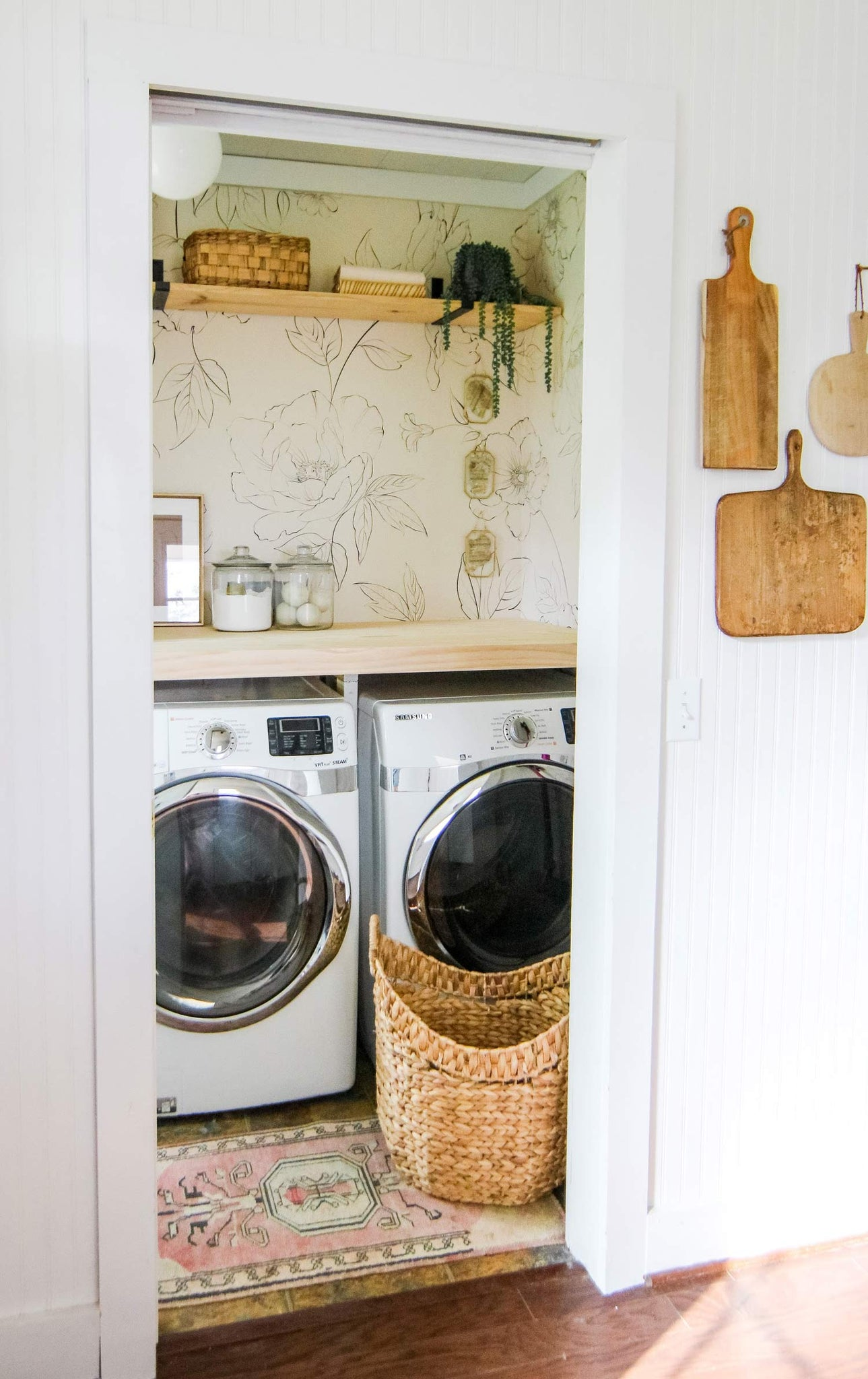 Small laundry room with oversized floral wallpaper and boho decor