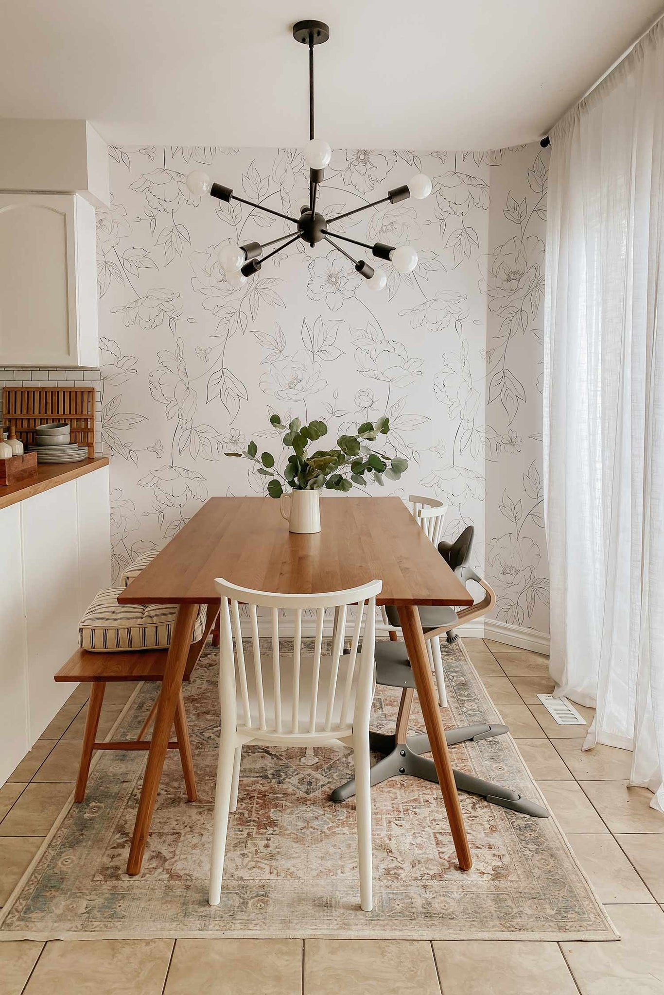 Minimal bohemian style dining room interior with oversized floral wallpaper accent wall