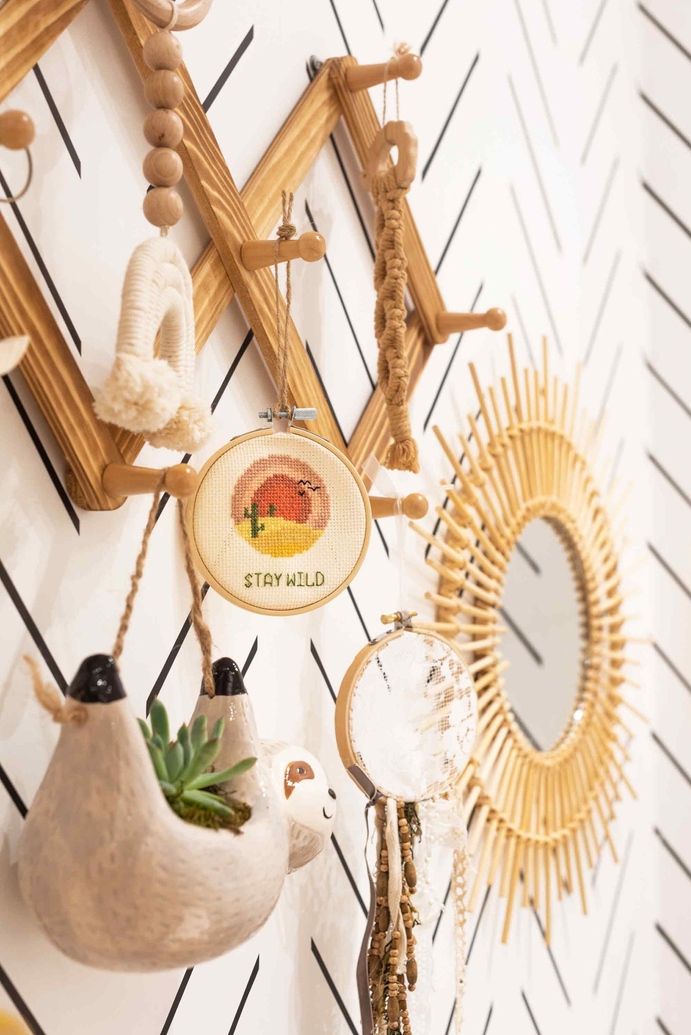 Hanging clothing rack in nursery interior with baby sloth planter and rainbow theme decor