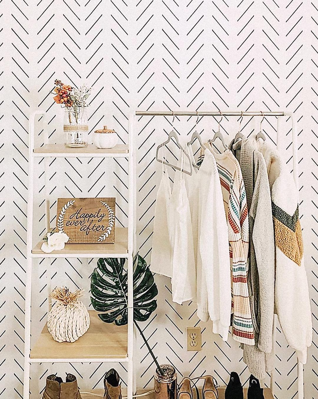 Walk in closet interior design with modern herringbone removable wallpaper, white and wood clothing rack and beautiful clothes display in bohemian farmhouse style