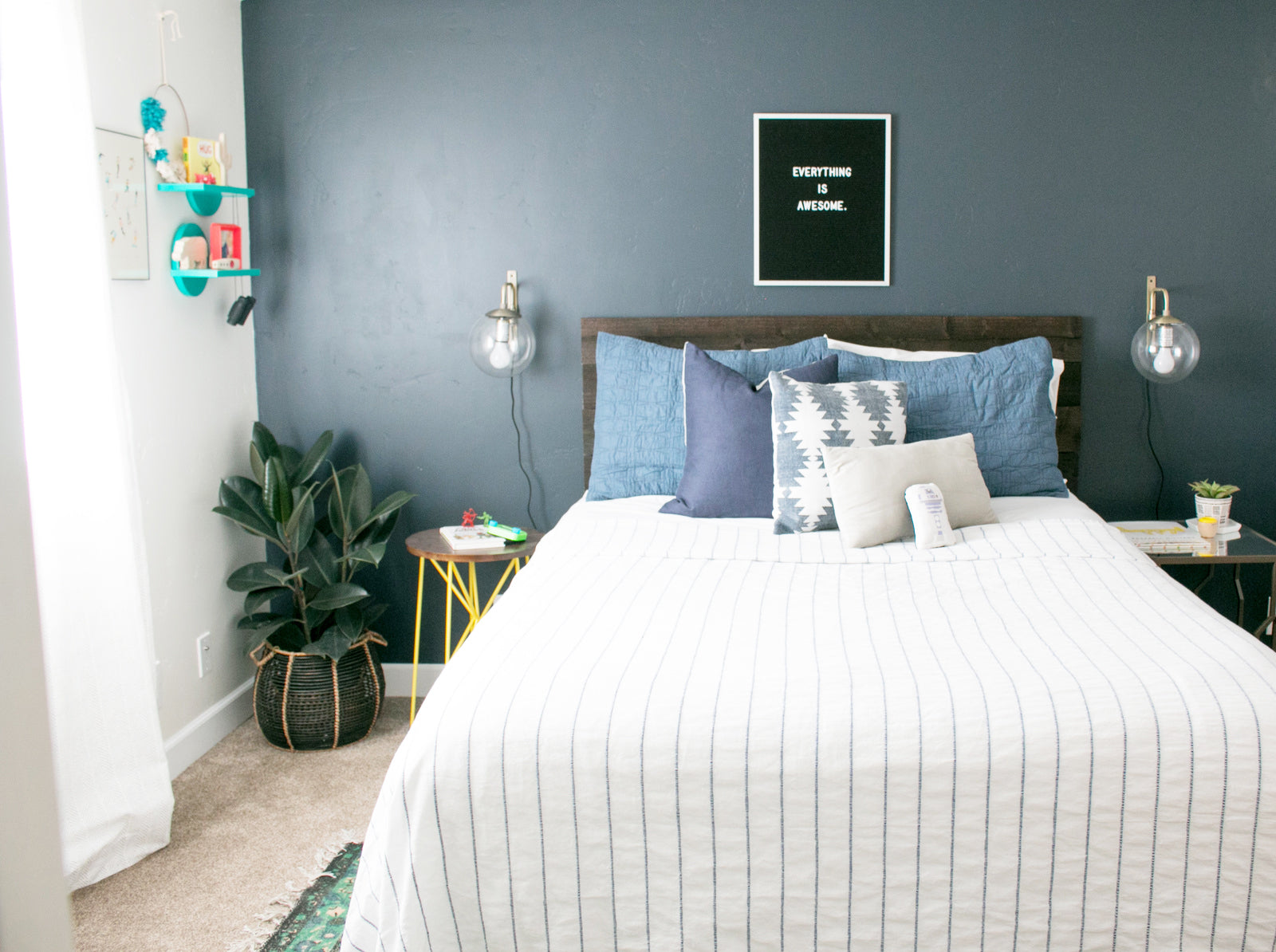 Navy blue accent wall in boys bedroom with ficus plant and yellow nightstand