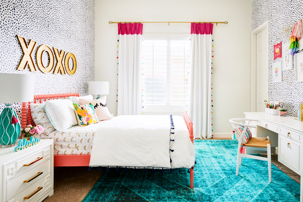Bright coastal style girl's room interior with turquoise rug and pink bed