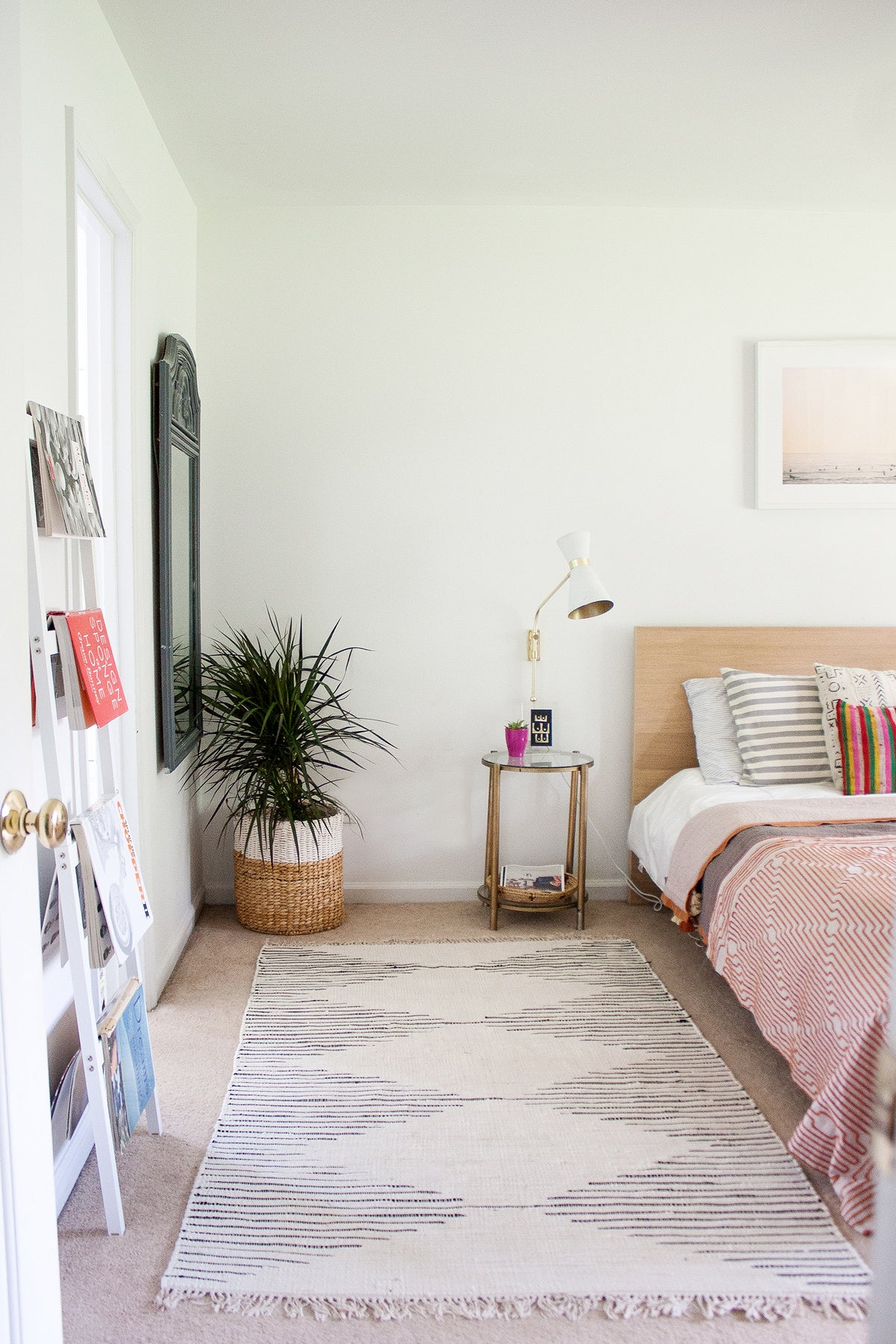 Simple eclectic master bedroom with moroccan rug and palms