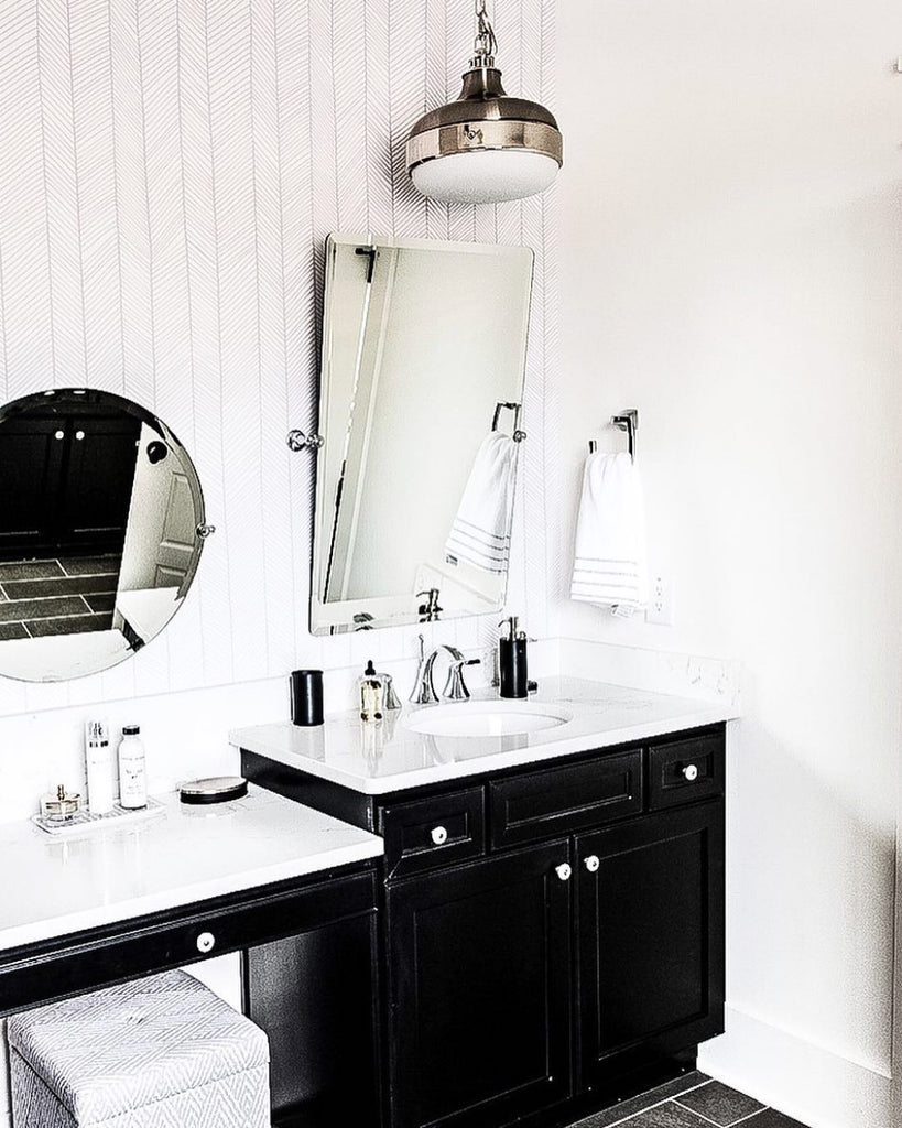 Chic bathroom interior with chrome fixtures, black vanity and removable wallpaper
