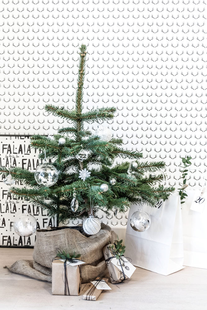 Christmas decor with antler wallpaper, kraft paper gift wrapping and Charlie Brown Christmas tree.