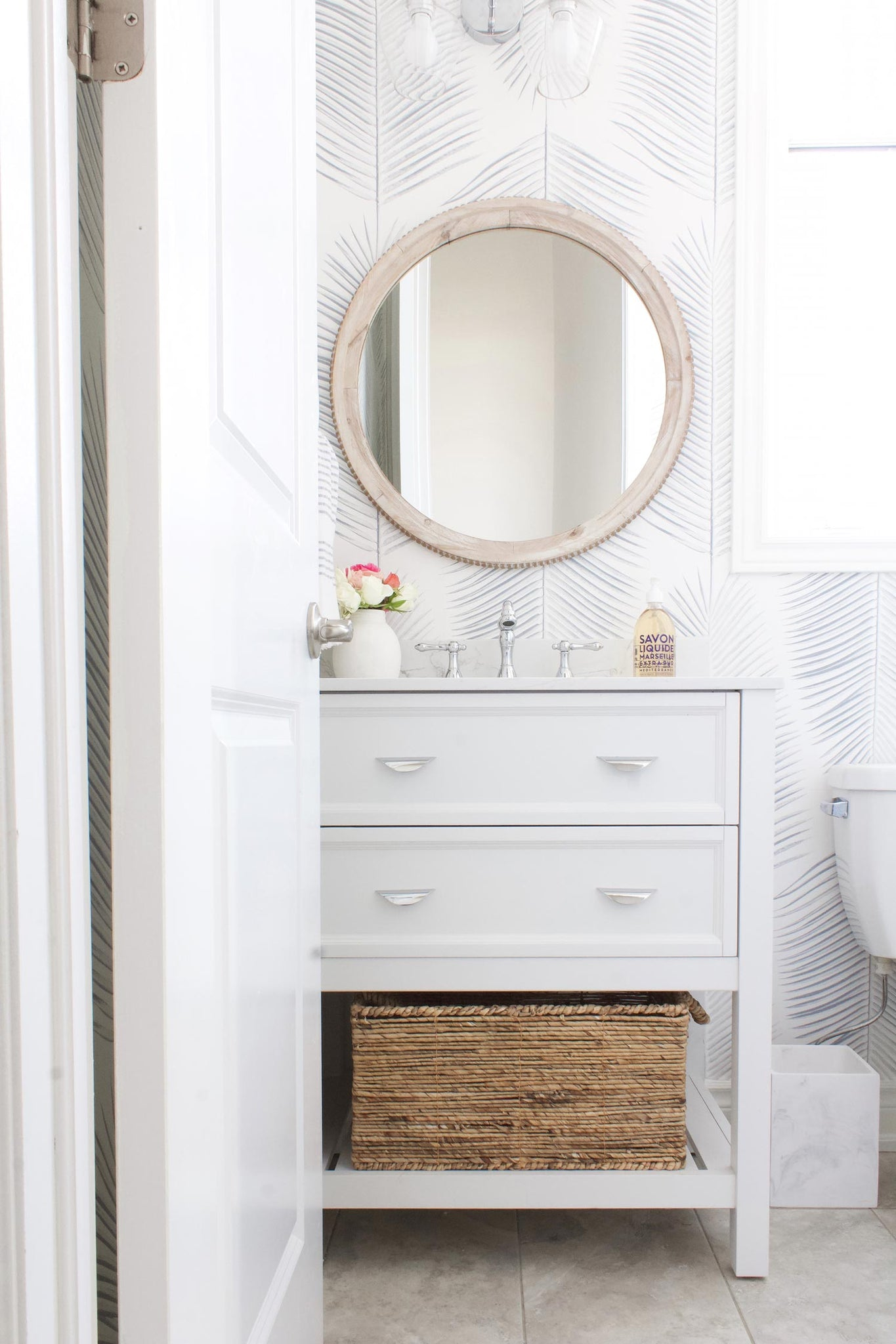 Coastal themed powder room remodel featuring traditional wallpaper with blue palm leave design