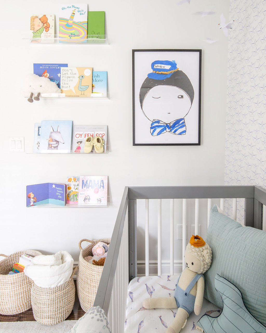 Nursery accent wall with captain poster and nautical theme colorful books on floating acrylic shelves