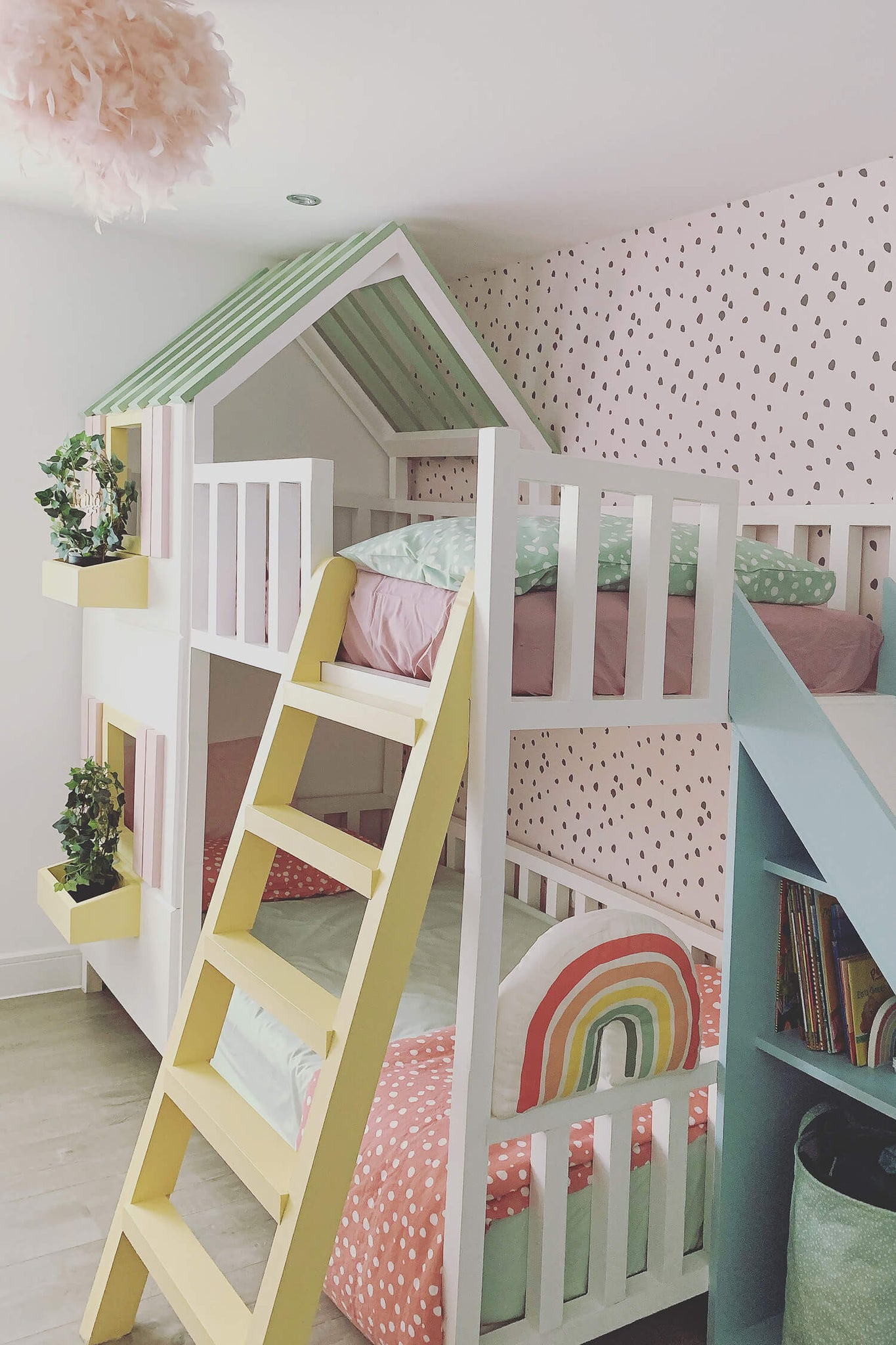 Modern girl's bedroom interior with white house bed and pastel pink removable wallpaper with rainbow theme