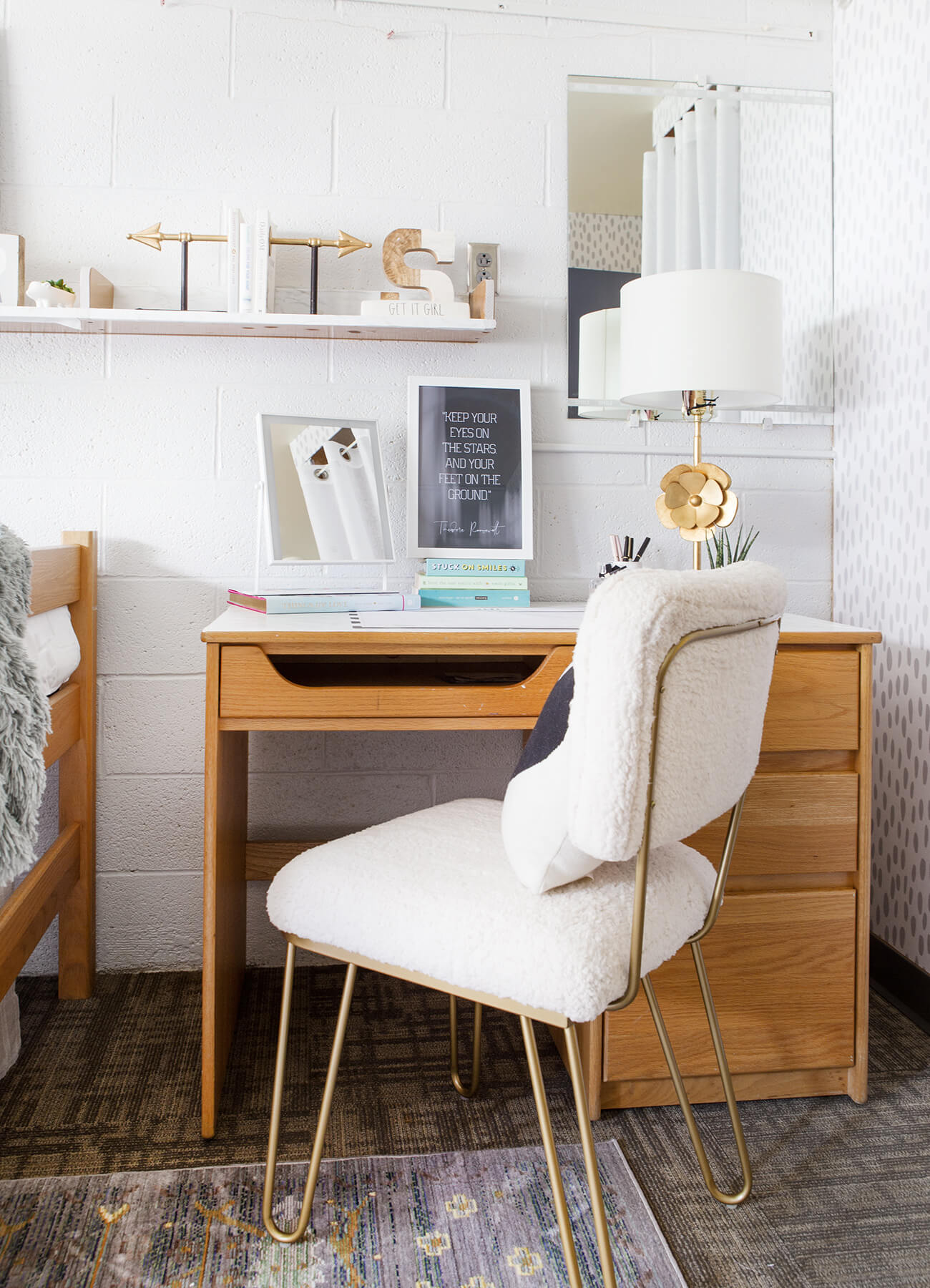 Dorm room work space, desk area with wood furniture, white and gold interior decor and desk accessories
