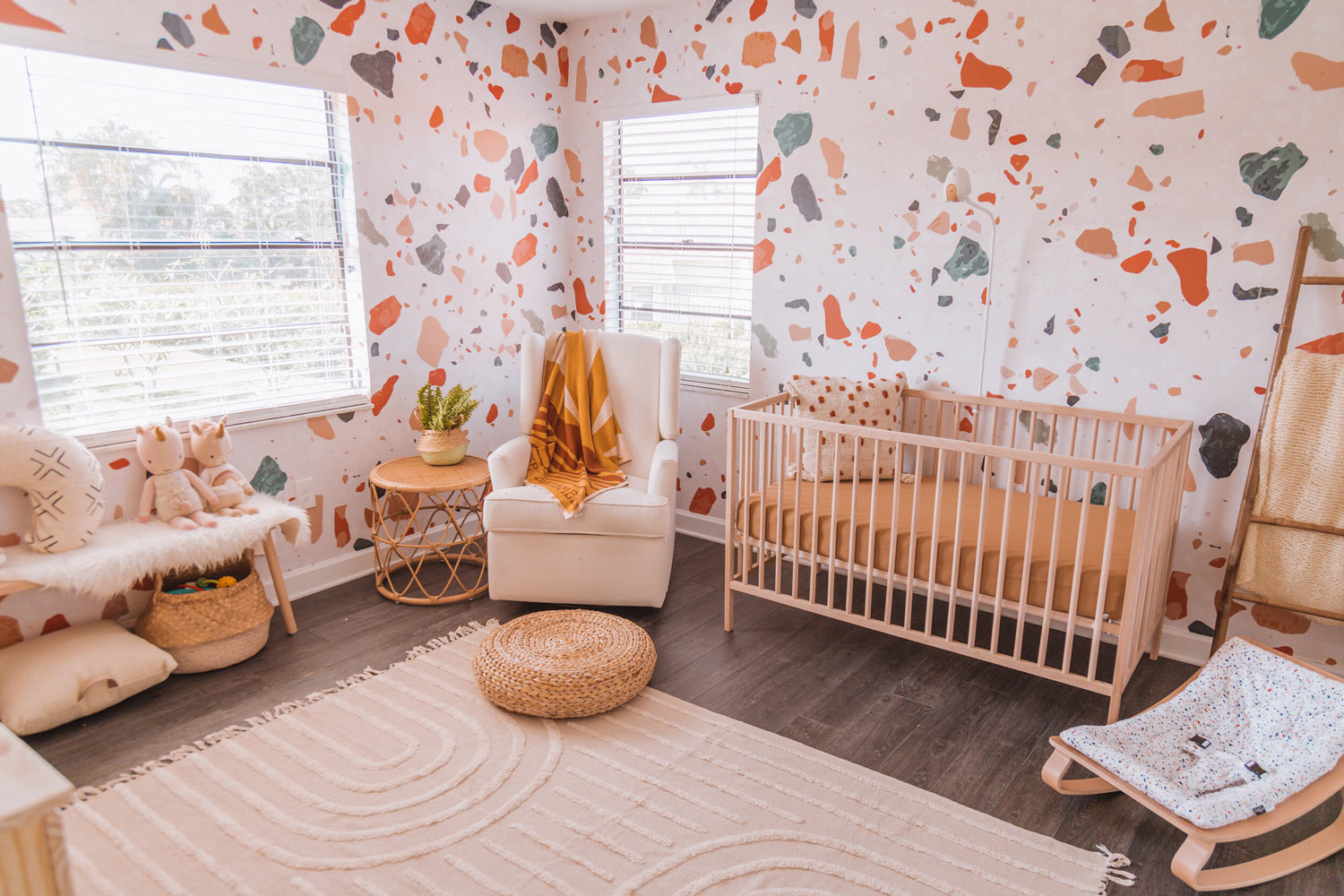 Warm tone baby girl nursery interior design with removable wallpaper feature wall