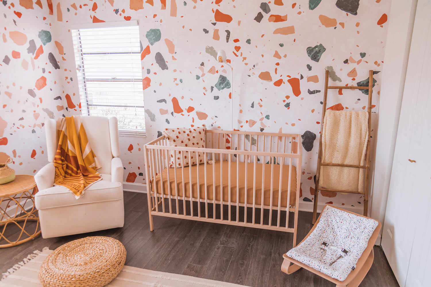 Warm tone gender neutral baby nursery interior room, with light wood ikea crib, livettes terrazzo removable wallpaper, eclectic bohemian interior style