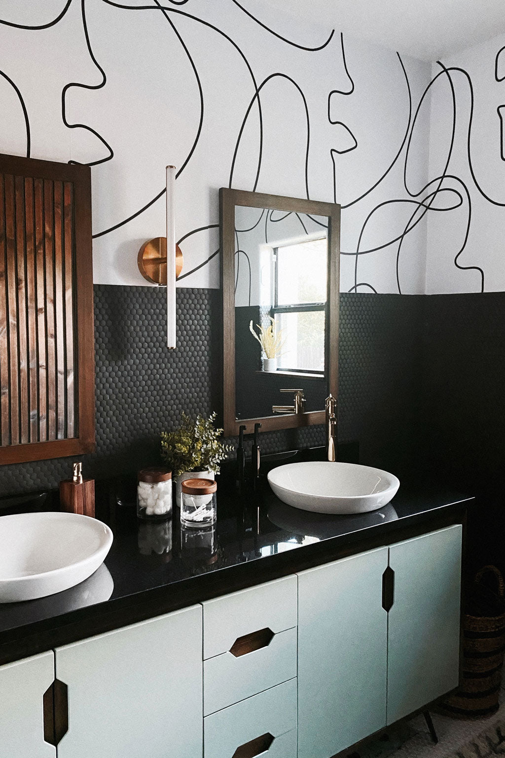 Mid century modern bathroom interior with peel and stick wallpaper and sage green vanity