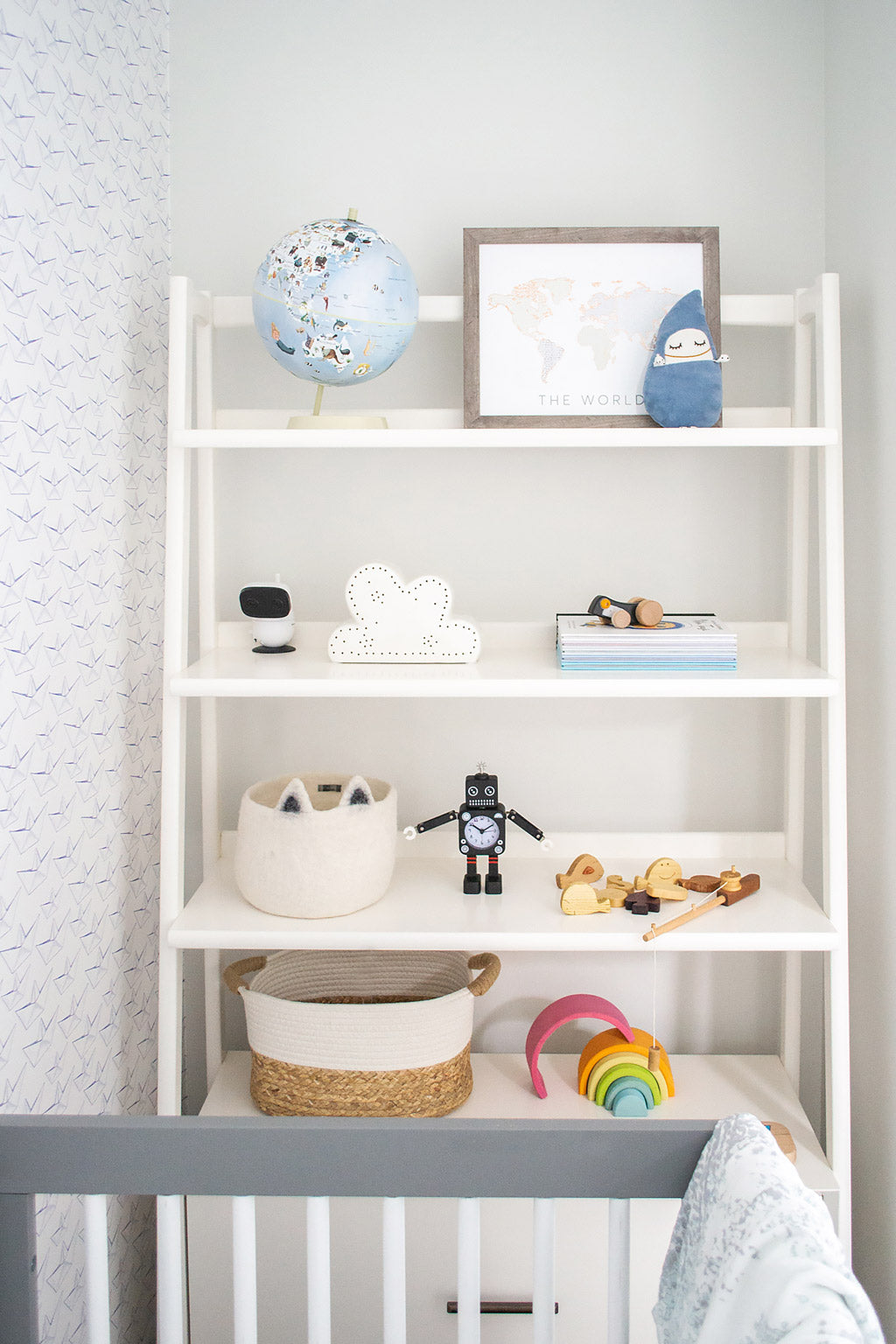 White ledge shelf with colorful nursery decor and books in white coastal baby boy nursery with paper boats removable wallpaper by Livettes