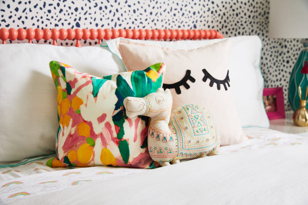Eclectic girls bedroom interior with floral cushions