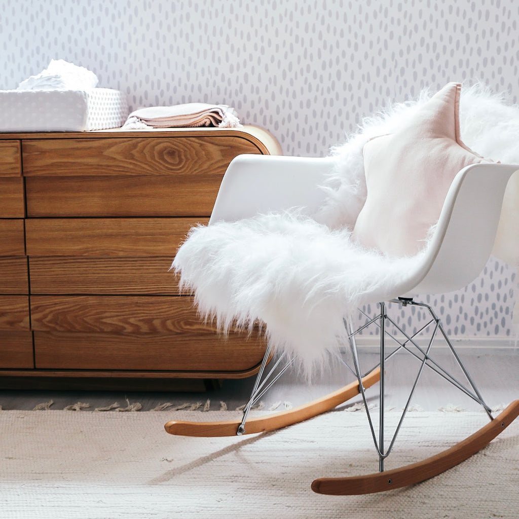 Nursery rocking chair with sheepskin rug and star shape pillow
