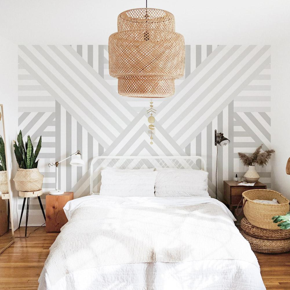 Bohemian bedroom interior with geometric removable wallpaper, rattan lamp and furniture, white bed linen and large mirror