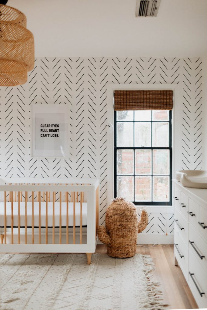 Minimal boho nursery with herringbone wallpaper, white wood crib and rattan cactus hamper