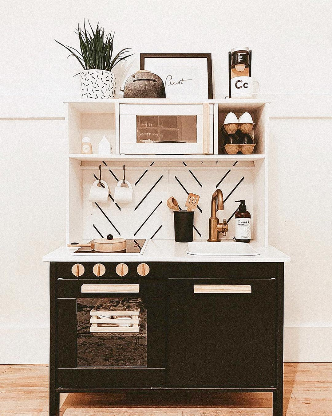 IKEA play kitchen DIY with modern herringbone removable wallpaper backsplash and black and brass kitchen hardware and decor