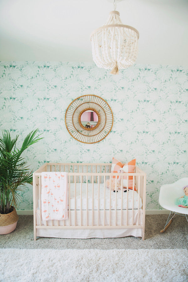 Subtle tropical nursery with monstera leaf wallpaper and flamingos