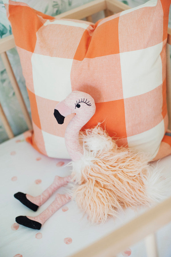 Flamingo plush toy with and a buffalo check throw pillow in a crib