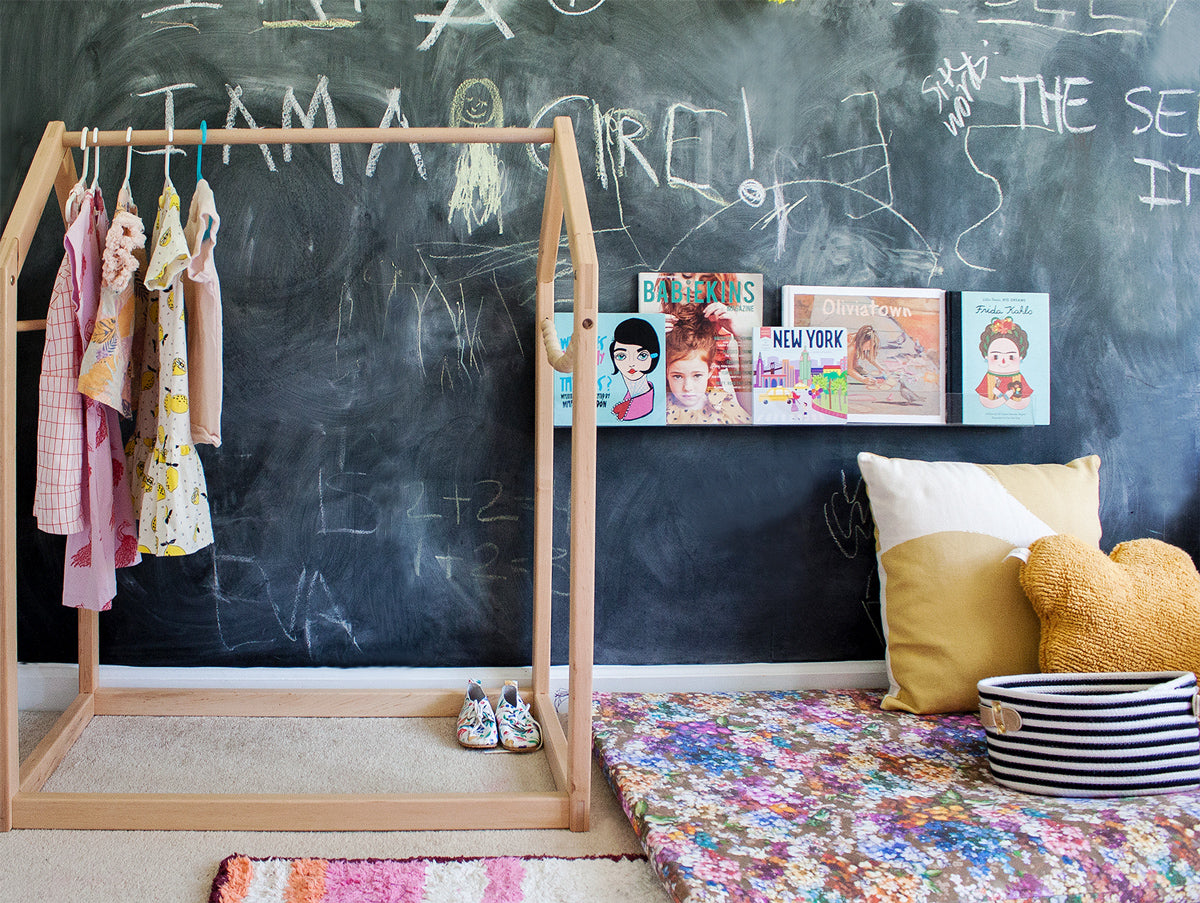 Kids room with chalkboard wall and colorful area rugs and wooden clothing rack