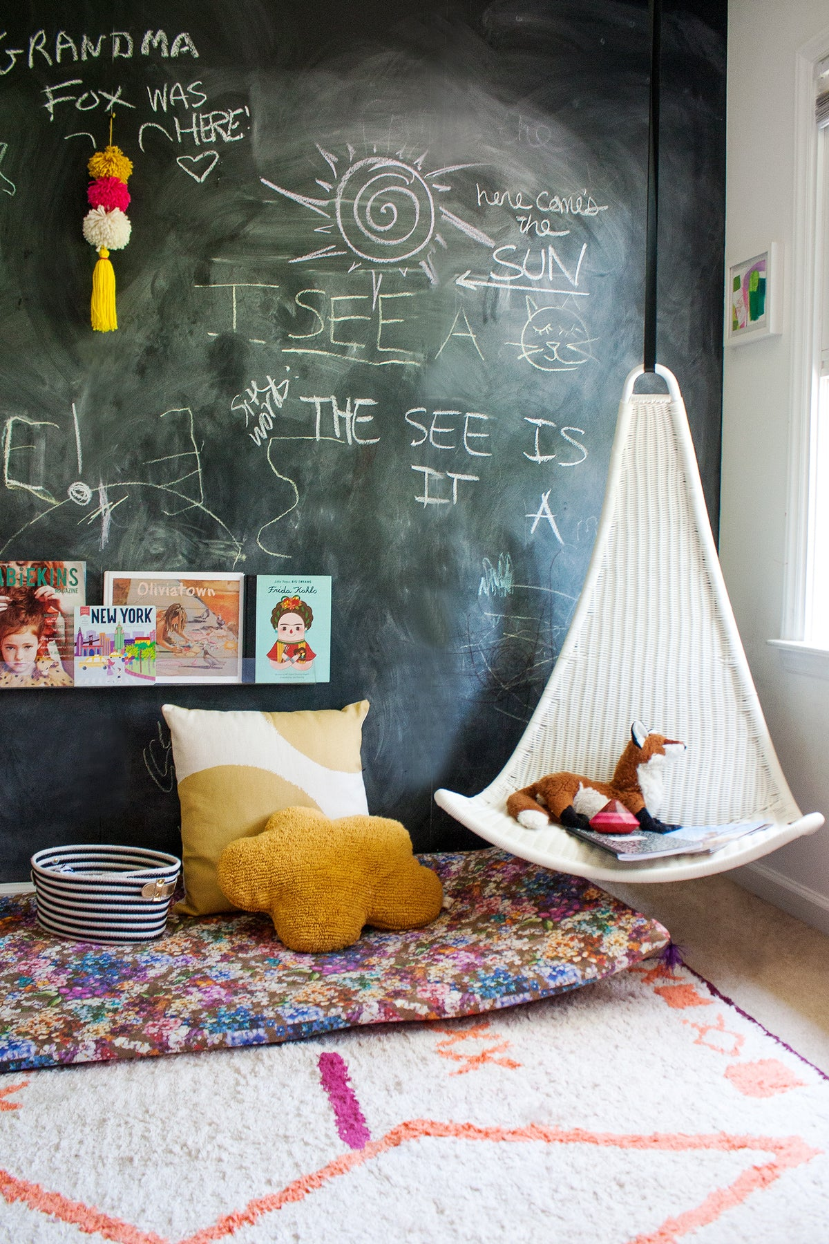 Kid's reading nook with bright rug and colorful pillows