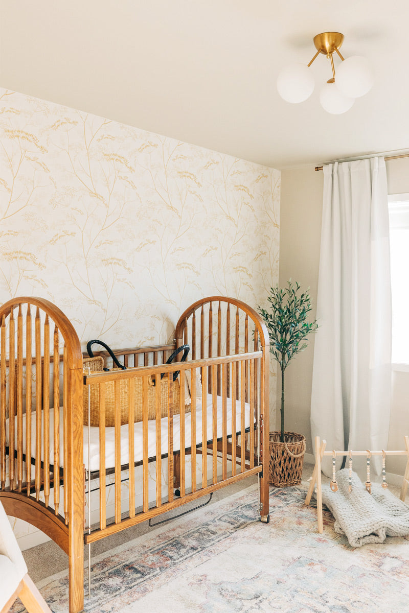 Modern farmhouse style nursery interior styled with botanical theme wallpaper