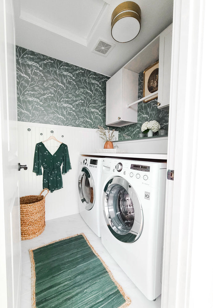 Stylish laundry room decorated with brass elements and green trendy removable wildflower wallpaper