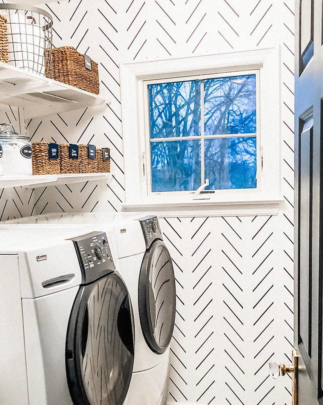 Black and white laundry room interior with white modern herringbone removable peel and stick wallpaper and glass organising containers and jute baskets
