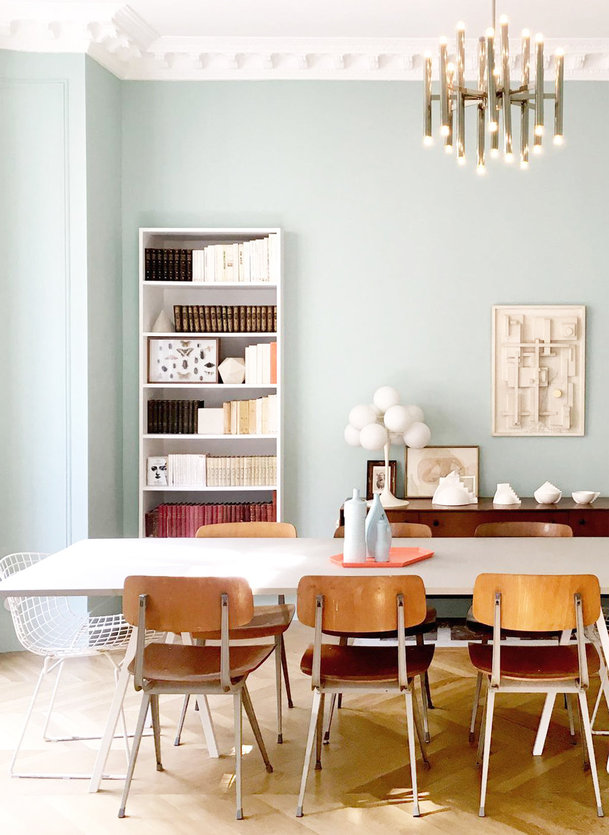 Parisian dining room with blue walls, modern furniture and gold chandelier