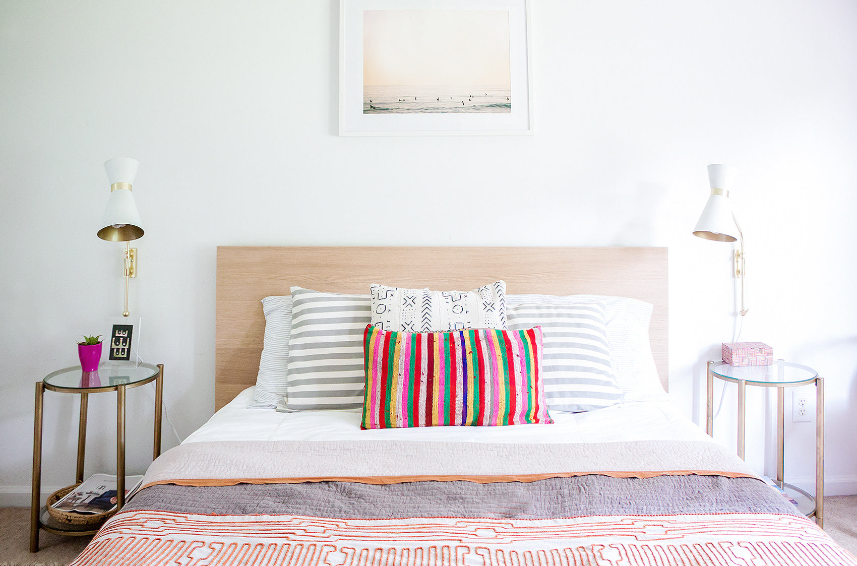 Simple master bed with colorful duvet and patterned cushions