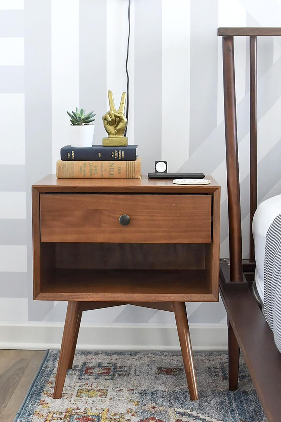 Mid century modern bedroom with dark wood nightstand, vintage books, light bed linen and black industrial wall sconces