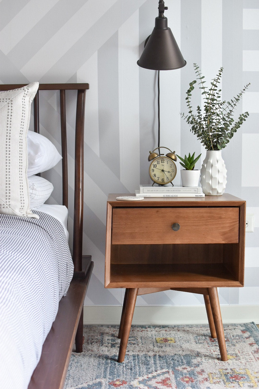 Mid century modern nightstand in master bedroom with geometric design removable wallpaper and neutral color bed linen