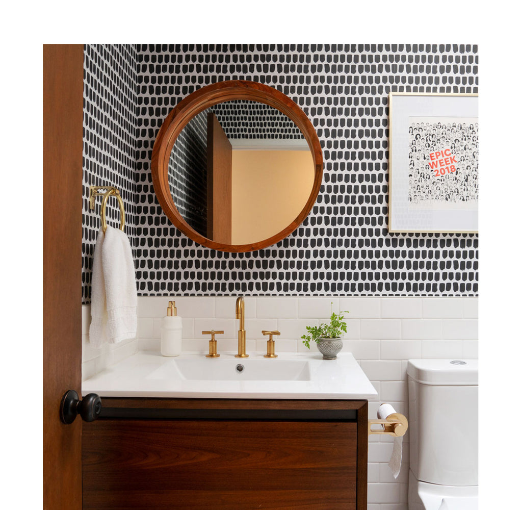 Mid-century modern powder room with bold removable wallpaper and brass decor