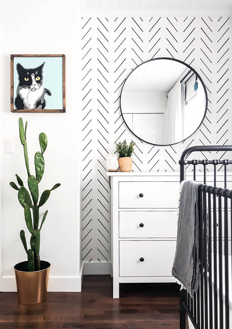Apartment Therapy inspired white nursery with herringbone removable wallpaper, large prickly pear cactus, black crib, round mirror and cat photo
