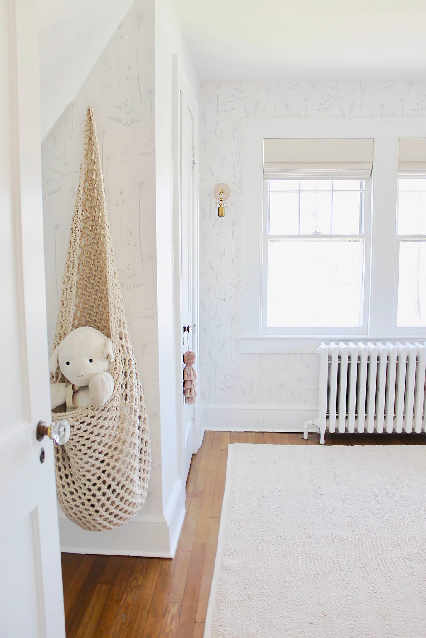 All white attic nursery interior with grey wildflower floral removable wallpaper and pink tassel decor