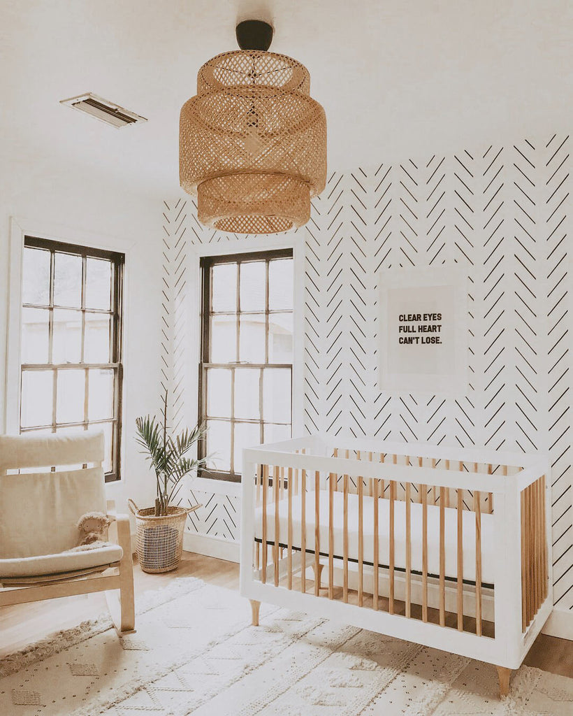 Minimal boho nursery with herringbone removable wallpaper