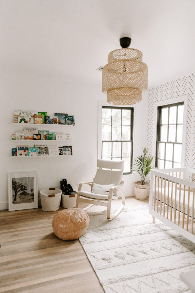 Minimal boho nursery interior with moroccan rug, white crib and leather ottoman