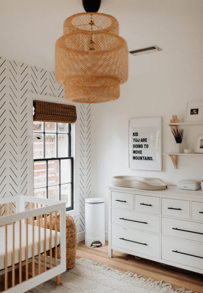 White minimal boho nursery with light wood accents and bohemian nursery decor